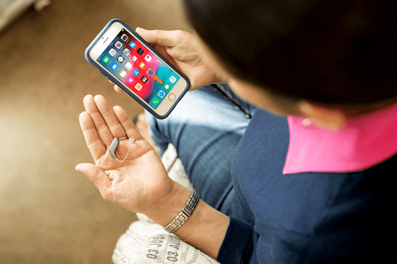 A woman looks at her smartphone while holding her hearing aid.